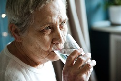 A beautiful old woman drinks water from a clear glass.