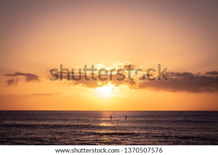 A beautiful orange and peach colored sunset with two stand up paddle boarders in the distance at Napili Bay on the island of Maui.  #1370507576