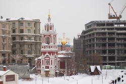 A beautiful Orthodox church with red brick walls and blue and gold domes in Zaryadye park between a construction site and a modern building
