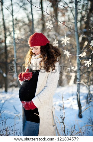 A beautiful outdoor pregnant woman portrait in snowy nature