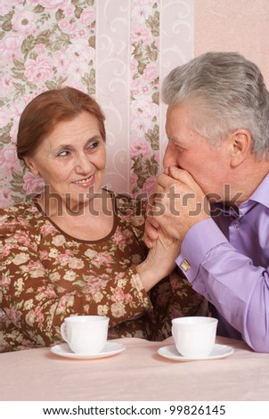 A beautiful pair of aged people sitting together on a pink background