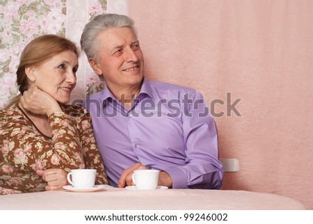 A beautiful pair of pensioner people sitting together on a pink background