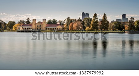 A beautiful panorama of City Park in Denver, Colorado in late summer or autumn. The brick boathouse and a row of trees changing color are reflected in the smooth, blue, peaceful water of the pond. #1337979992
