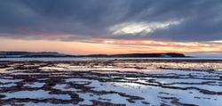 A beautiful panorama sunset over the ocean with rocky beach and tidal pools in the foreground