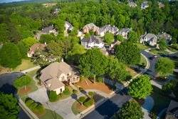 A beautiful Panoramic aerial view of cluster of beautiful houses, landscaped yards and fresh spring bloom on trees in an upscale subdivision in Suburbs of Georgia shot during golden hour.