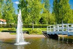 A beautiful park with a pond, wooden bridge and fountain in sunny summer day