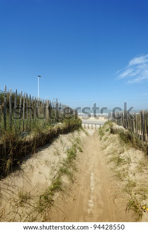 A beautiful path through the dunes and Marram grass against blue sky with end to the sea. Useful file for your brochure about European sea coast, ecology and eco tourism.