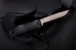 A beautiful photo of a black knife on a black background. Large hunting knife. Top.