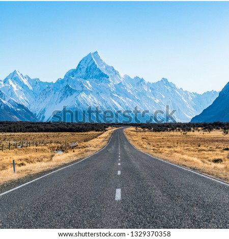A beautiful picture of a rode and a  mountain