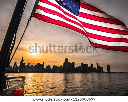 A beautiful picture of an American Flag rippling in the wind over the Chicago skyline at sunset with building silhouettes and orange colored sun reflecting on the water of Lake Michigan.