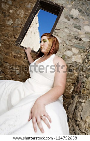 A beautiful plus size bride with green eye make-up posing in her wedding dress