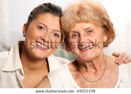 A beautiful portrait of grandma and granddaughter smiling over white background - stock photo