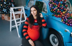 A beautiful pregnant brunette girl is sitting near a blue retro car decorated with balls and gifts in a modern studio with New Year's and Christmas decorations. Happy woman expecting a baby.