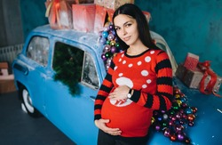 A beautiful pregnant brunette girl is standing near a blue retro car, decorated with balls and gifts, in a modern studio with New Year's and Christmas decorations. Happy woman expecting a baby.