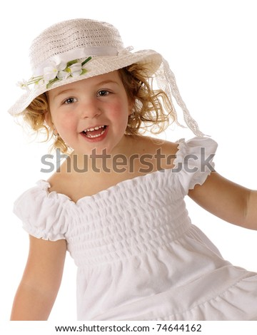 A beautiful preschooler delighted with her white Easter bonnet and dress.
