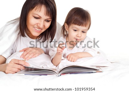 A beautiful pretty Caucasian mother with her daughter lying on the bed with a book