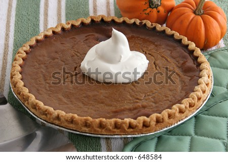 A beautiful pumpkin pie ready to serve with whipped cream.