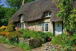 A beautiful quaint Cotswold country Thatched Cottage and garden in summer in the heart of The Cotswolds, Gloucestershire, United Kingdom