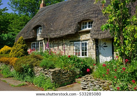 A beautiful quaint Cotswold country Thatched Cottage and garden in summer in the heart of The Cotswolds, Gloucestershire, United Kingdom Foto d'archivio ©