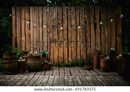 A beautiful recreation area in the park or in the garden. Wooden terrace, rustic loft interior. Retro garland with luminous bulbs, decorated pots with flowers and candles #691783375