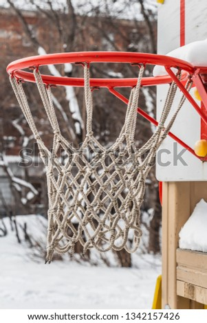 A beautiful red basketball hoop with white rope net and white snow on the children's playground in the yard in winter. Vertical photo