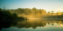 A beautiful river morning with mist and sun light. Springtime scenery of river banks in Northern Europe. Warm, colorful look.