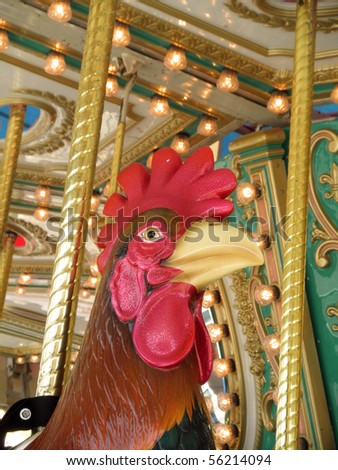 A beautiful Rooster on a carousel ride at an amusement park.