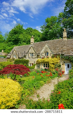 A beautiful row of picturesque cottages and gardens in summer with blue sky and clouds, The Cotswolds, Gloucestershire, United Kingdom #288715811