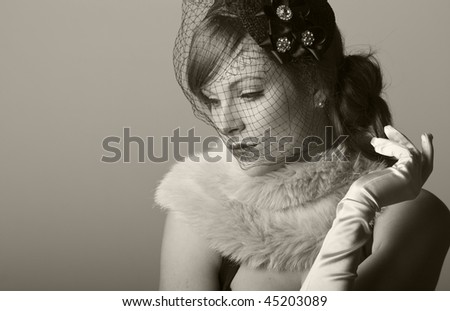 a beautiful 1930s inspired woman in a net veil and furry stole