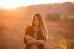 A beautiful sad girl with long red hair stands alone alone, warms herself with her hands, looks at the camera, does not smile against the sunset. Traveling alone, freedom, self-knowledge. Close up