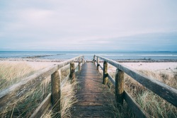 A beautiful scenery of a wooden pathway leading to the beach for a relaxing day