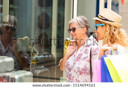 A beautiful senior female enjoys shopping together with her best friend.  In their hands a lot of shopping bags with gifts for the incoming christmas. Two women. Consumerism concept