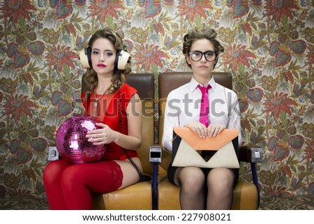 a beautiful sexy disco woman in a train chair filmed twice interacting with herself. One of her characters is serious the other playful