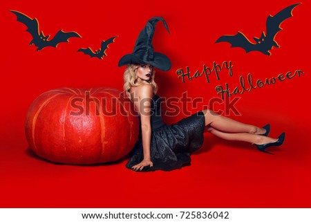 A beautiful sexy girl witch in a black dress and pride sits on a red background near a large orange pumpkin. Halloween.Thanksgiving, All Saints Day, holiday, discounts, sales, postcard, fashion.