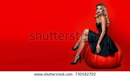 A beautiful sexy girl witch in a black dress and pride sits on a red background near a large orange pumpkin.