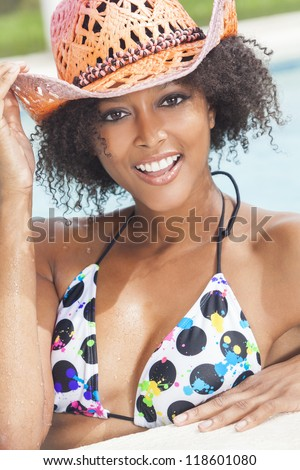 A beautiful sexy young African American girl or young woman wearing a bikini and straw cowboy hat laughing on the side of a swimming pool.