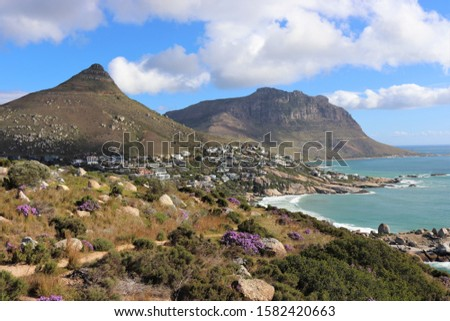 A beautiful shot of a dry grassy field with flower and buildings on the side of the mountain under a cloudy sky #1582420663