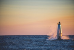 A beautiful shot of a lighthouse in the middle of the sea with a pink sky in the background