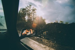 A beautiful shot of a photographer reflected in the car's side mirror with a blurred road and trees in the background