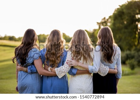 A beautiful shot of four female with their arms around each other and a blurred background Stock photo ©