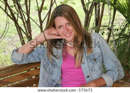 stock photo : A beautiful, shy teen girl on a porch swing.