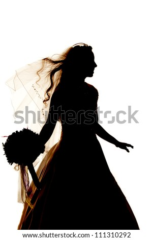 A beautiful silhouette of a beautiful young bride holding flowers.