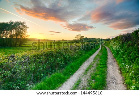 A beautiful sky after sunset on a summer farm track and fields in England, UK with red, orange and pink sky elements