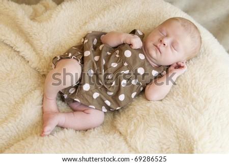 A beautiful sleeping baby girl on a blanket