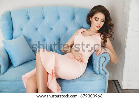 A beautiful slender brunette woman in a pink dress with flounces is sitting on a blue velvet armchair