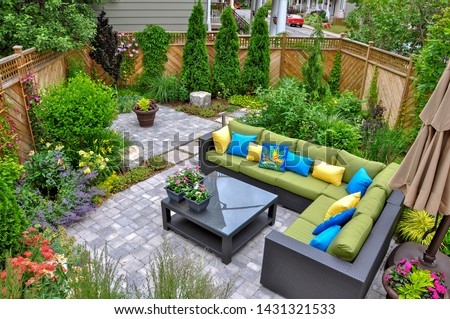 A beautiful small, urban backyard garden featuring a tumbled paver patio, flagstone stepping stones, and a variety of trees, shrubs and perennials add colour and year round interest. #1431321533