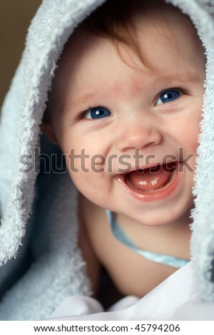 A beautiful smiling baby wrapped in a furry blue blanket