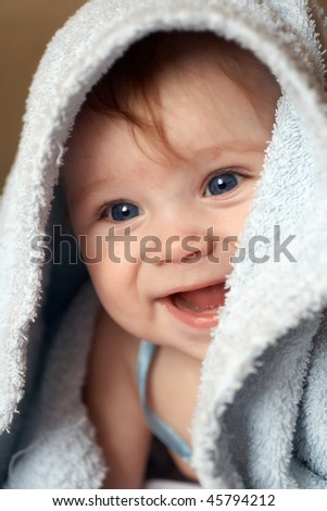 A beautiful smiling baby wrapped in a furry blue blanket A beautiful smiling baby wrapped in a furry blue blanket