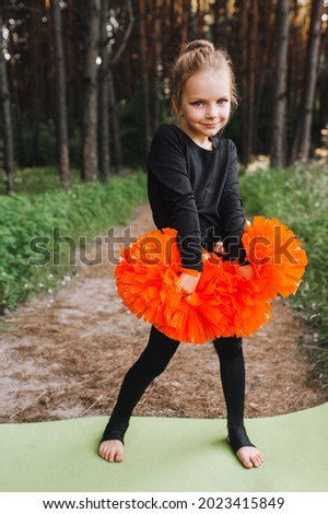 A beautiful, smiling girl, a child cheerleader in a black suit dances, performing movements, in the forest on a green rug with orange pom-poms in her hands. Sports training for cheerleading. ストックフォト ©
