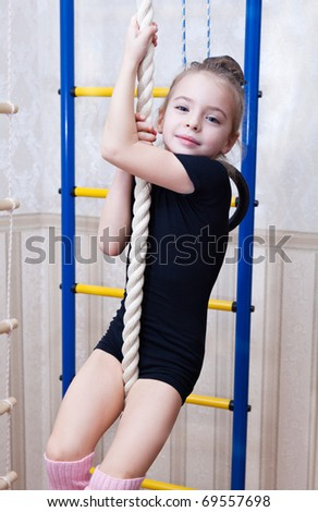 a beautiful smiling girl climbs on a rope